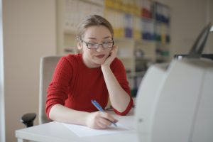 Woman wearing red and glasses happily writing