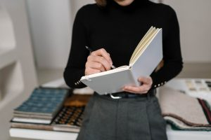 Woman stood up wearing black writing in notebook