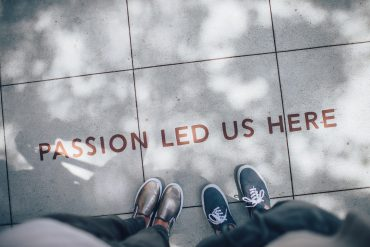 Overhead view of two people stood on pavement that reads 'passion led us here'