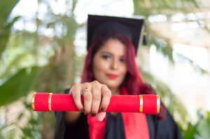 Woman holding degree out - closeup