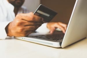 Man holding credit card over laptop