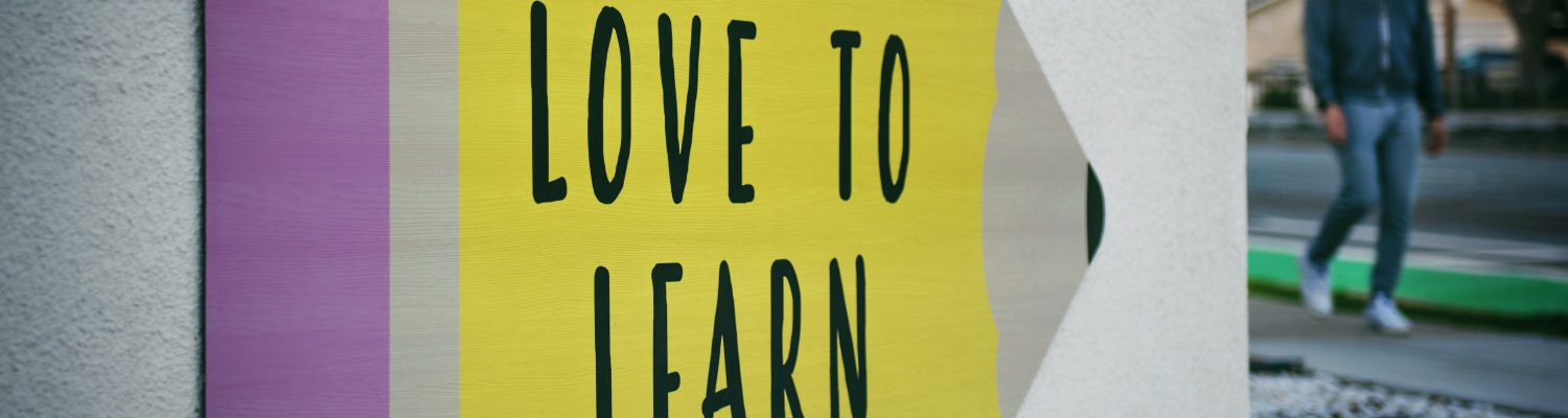 Sign with giant pencil and text that reads 'Love to Learn'