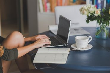 Woman typing at laptop with notebook and coffee cup