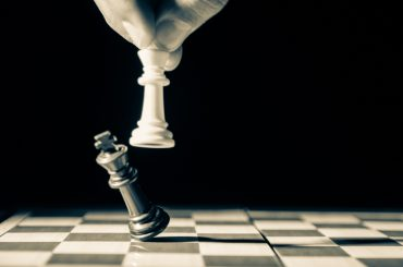 Artistic closeup of white chess piece dislodging black chess piece