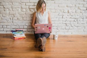Woman sat on wooden floor using pink laptop with books next to her