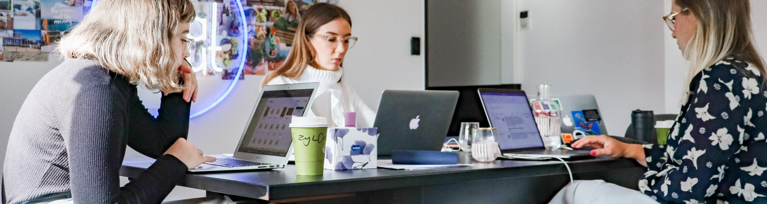 Group of young professionals sat around a hot desking desk with laptops
