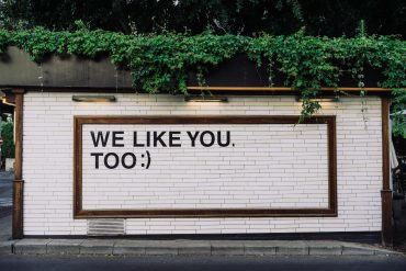 Street billboard with white bricks and the words 'We like you too :)' in black type
