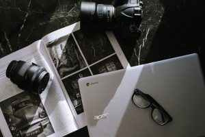 Collection of magazine clippings, laptop and camera
