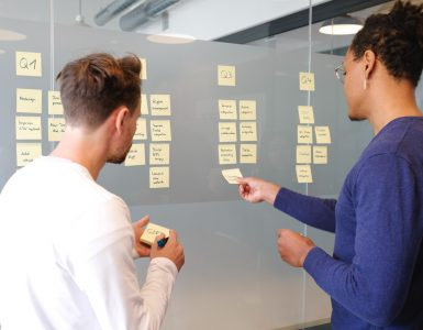 Man and woman adding post-its to a glass wall
