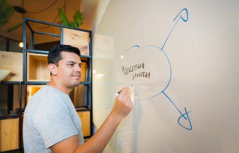 man stood in front of whiteboard writing out marketing strategy