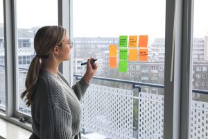 Woman writing on postit notes stuck to glass window