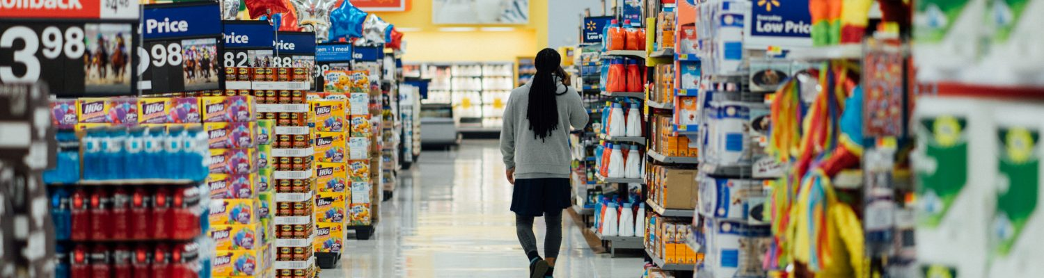 View of someone walking down a supermarket aisle