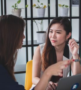 Two women having a conversation over a laptop