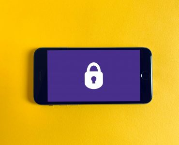 Smartphone in landscape mode against a yellow background with an image of a padlock on the screen