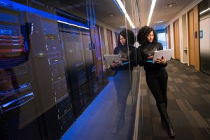Woman leaning against a server room using a laptop