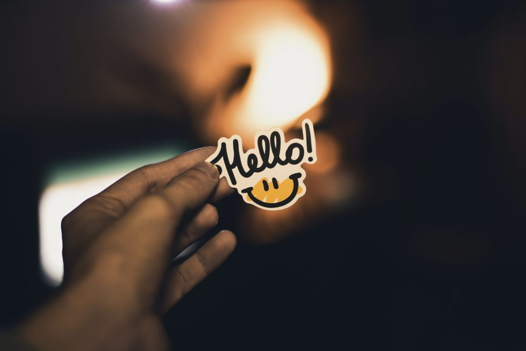 Person holding a sticker that says 'hello' with a smile