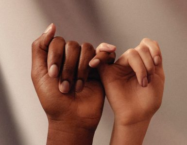 Two hands holding pinkie fingers