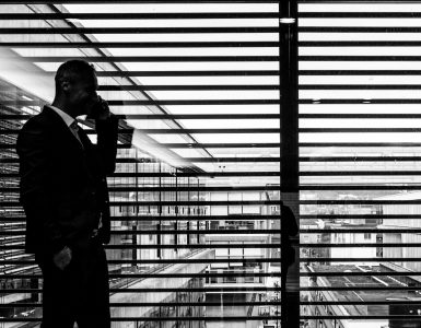 Businessman on the phone walking past a window