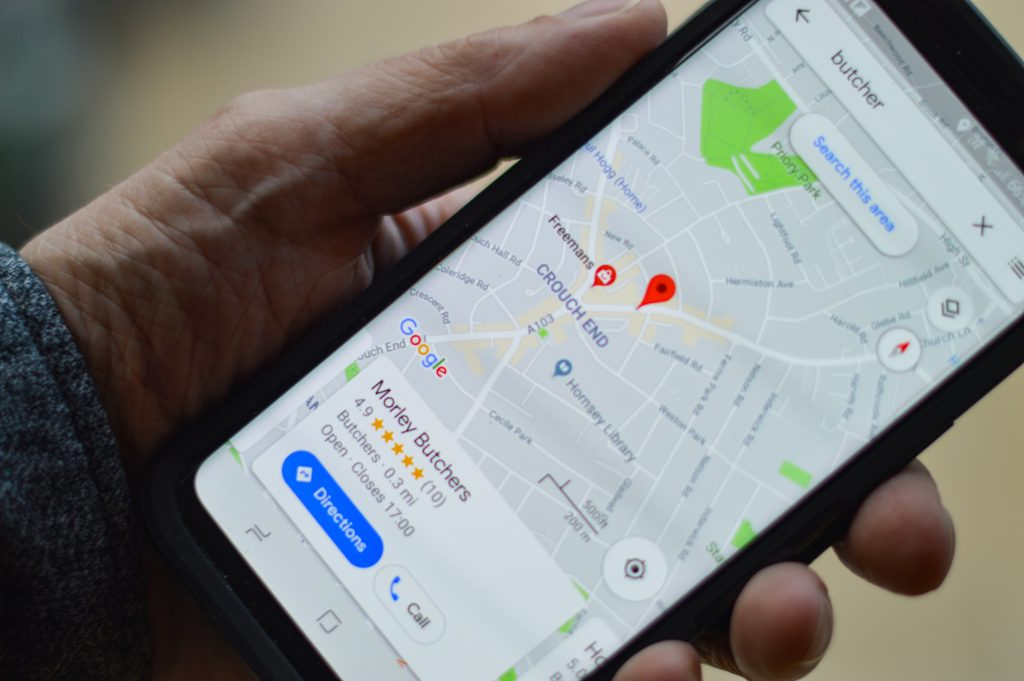 Person holding a phone with a local service ad on a map - How does advertising increase brand awareness - Copify blog
