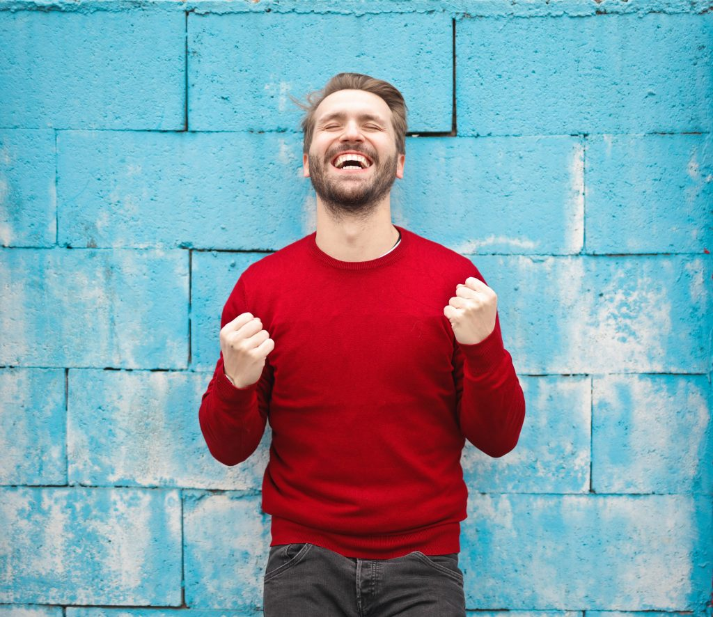 Man wearing red jumper against a blue brick background celebrating - How does advertising increase brand awareness - Copify blog