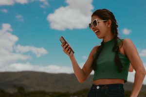 A woman laughing, looking at her phone