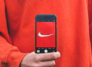 Person holding up a smartphone in front of them with the Nike tick logo, what is brand awareness definition