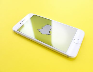White iphone against yellow background with snapchat icon - What is content creation in social media