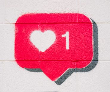 Image of a pink like icon with a white heart spraypainted onto a wall - Who does content marketing well - Copify blog