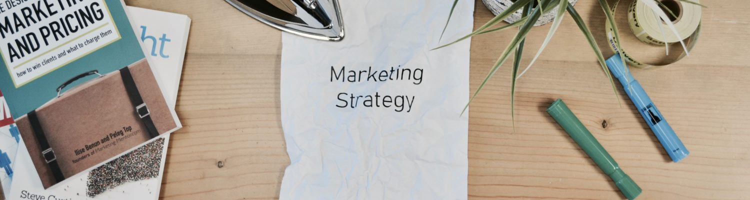 marketing strategy on piece of paper with plant and pen surrounding