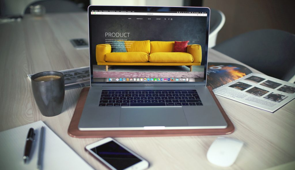 laptop and phone on table screen showing yellow sofa product