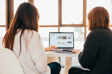 Image of two women looking at content on a laptop - How to update website content online - Copify blog