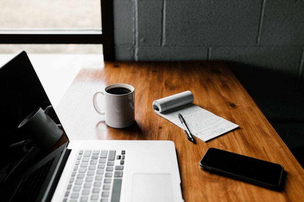 Image of a laptop on a desk next to a notepad - How to update website content online - Copify blog