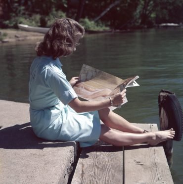woman reading old magazine by side of water