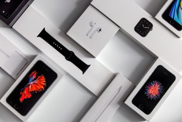 selection of Apple products in boxes including watch, phone and airpods