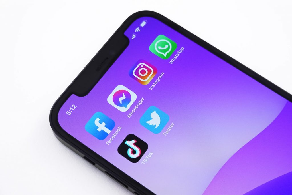 iPhone with purple backdrop and various social media apps