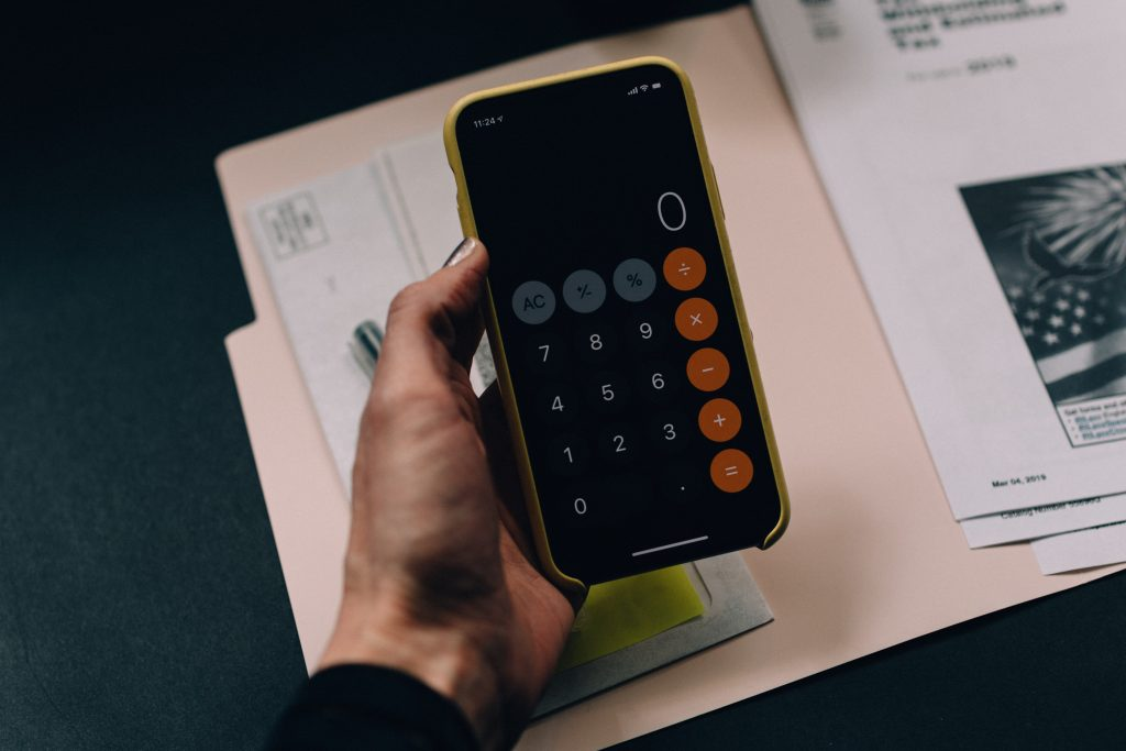 Image of someone using a calculator - How does brand awareness impact sales - Copify blog