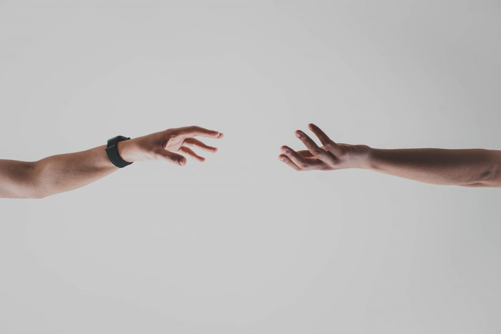 Image of two hands reaching out and almost connecting - How does social media support content marketing - Copify blog