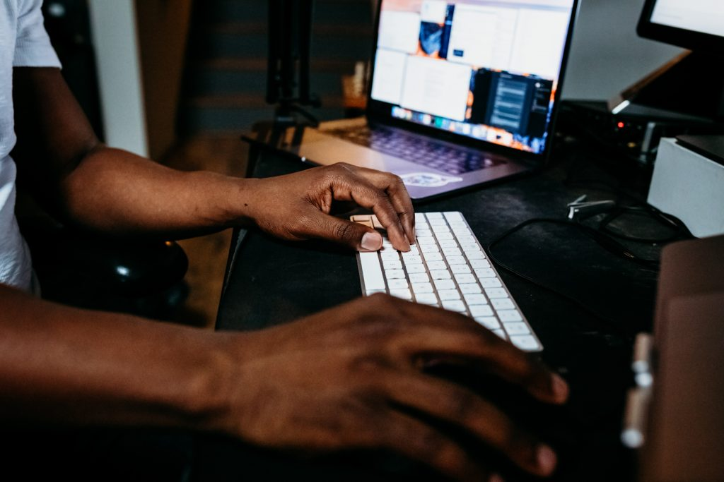 Image of hands typing and a desktop screen in background