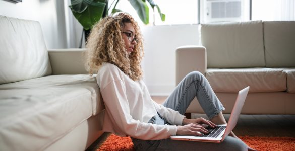 Woman sat on floor looking at laptop - How to check unique content online free - Copify blog 1
