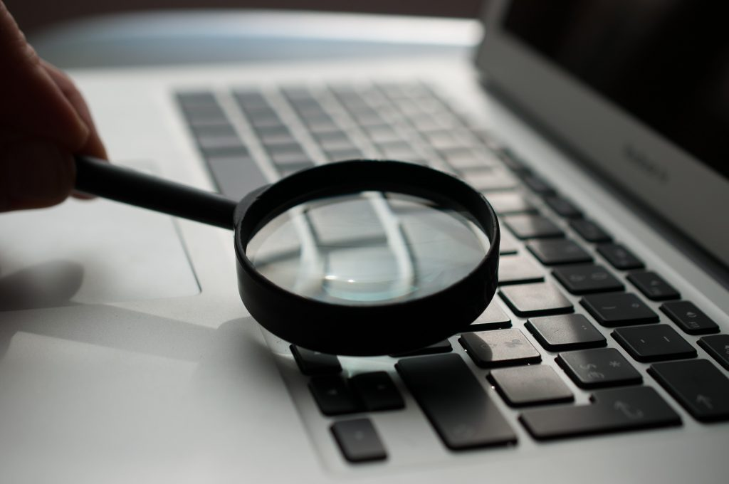 Magnifying glass on laptop keyboard - How to check unique content online free - Copify blog 1