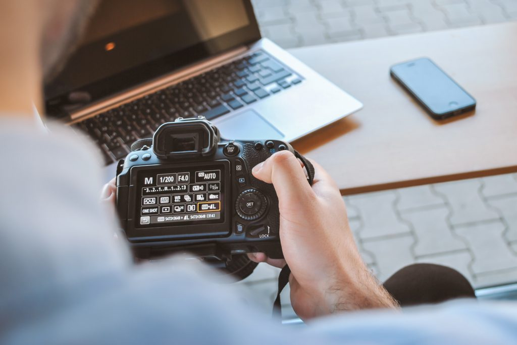 Image of someone sat at a desk looking at a DSLR camera - How to market my ecommerce store - Copify blog