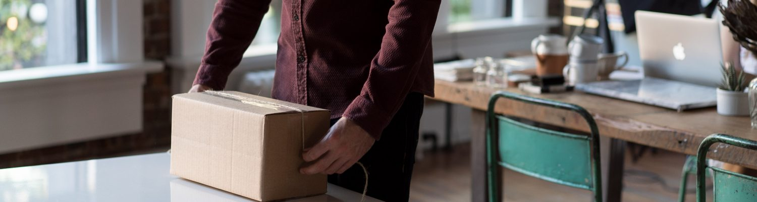 Image of a man boxing up goods - How to market my ecommerce store - Copify blog