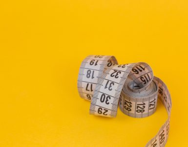 Image of a measuring tape on a yellow backgroung - How to measure SEO effectiveness - Copify blog