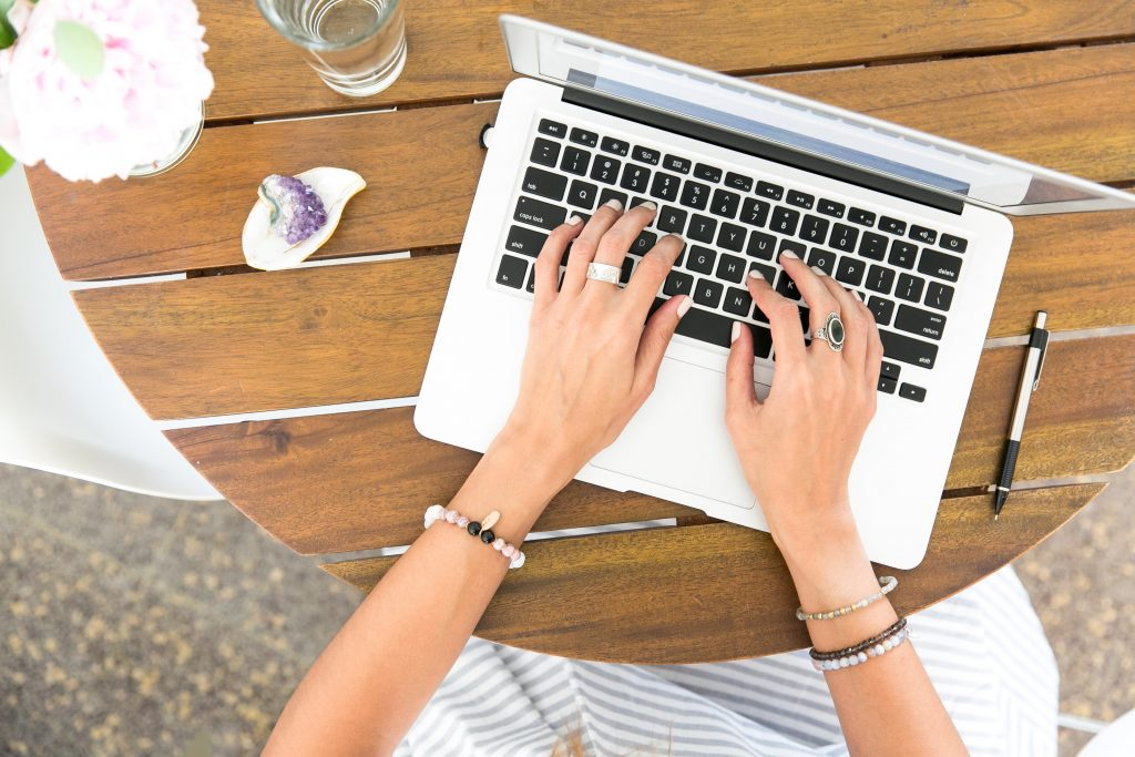 Overhead view of someone typing on a laptop - How to raise brand awareness online - Copify blog