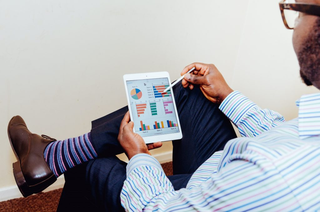 Image of a man looking at metrics on a tablet - How to raise brand awareness online - Copify blog