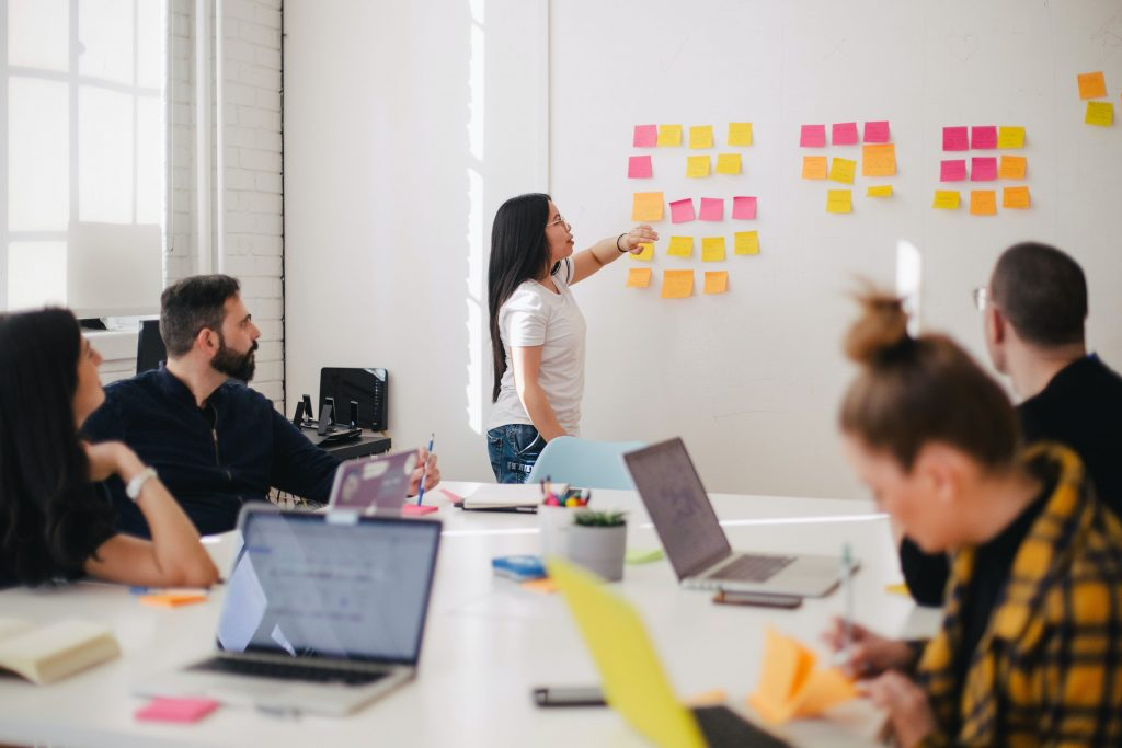 Image of a woman creating a strategy using post it notes - how big is the content marketing industry - Copify blog