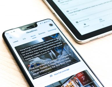 Image of a smartphone showing news article next to a table - What is content syndication in SEO - Copify blog